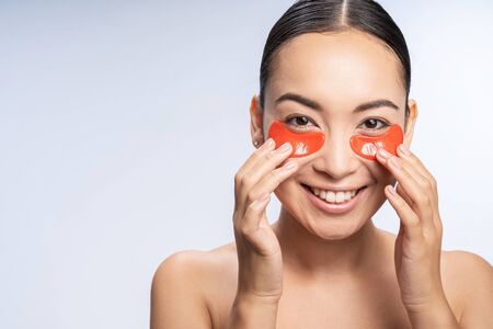 Smiling sexy girl takes care of her skin against light background. Beauty procedures concept Imagens