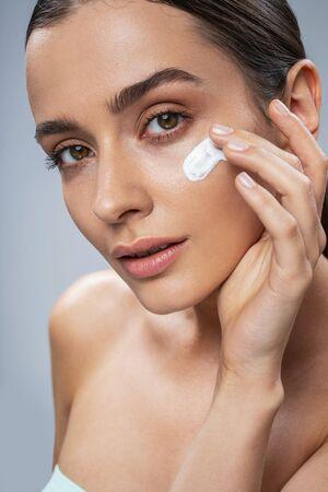 Caucasian amazing lady applying facial cream. Beauty procedures concept