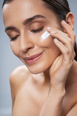 Caucasian calm lady applying facial cream. Beauty procedures concept