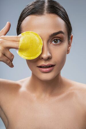 Cute charming young lady taking care of facial skin. Beauty procedures concept