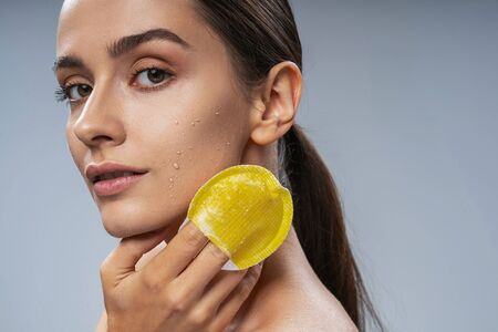 Cute young woman taking care of facial skin. Beauty procedures concept