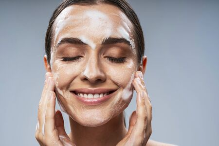 Happy Caucasian lady taking care of facial skin. Beauty procedures concept Stock Photo