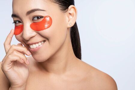 Happy cute woman takes care of her skin against light background. Beauty procedures concept