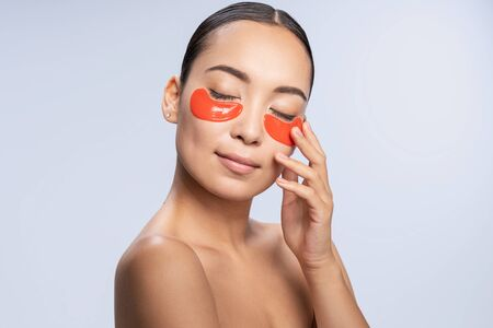 Charming young lady takes care of her skin against light background. Beauty procedures concept