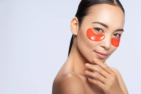 Charming Asian girl takes care of her skin against light background. Beauty procedures concept Imagens
