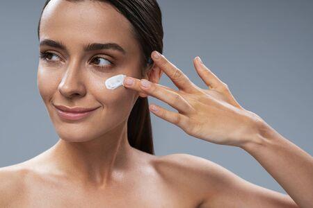 Caucasian nice lady applying facial cream. Beauty procedures concept