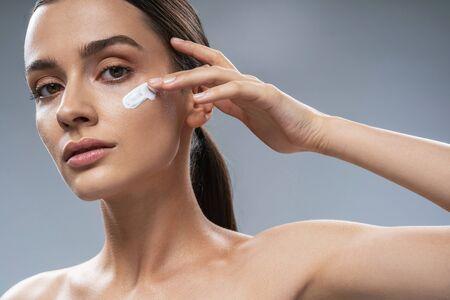 Caucasian pretty lady applying facial cream. Beauty procedures concept