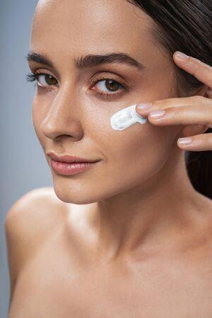 Caucasian charming lady applying facial cream. Beauty procedures concept Stock Photo