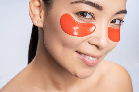 Charming young lady making beauty procedures for skin indoors. Personal care concept