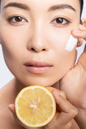 Attractive Asian girl posing for camera with lemon. Personal care concept