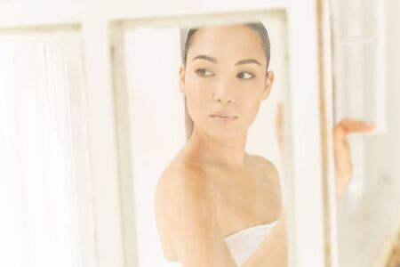 Concentrated Asian sexy girl standing near window. Personal care concept