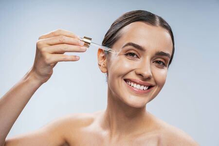 Sexy young lady using facial serum. Beauty procedures concept Stock Photo