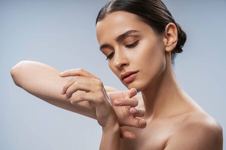 Cute young lady using perfume at home. Beauty procedures concept