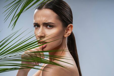 Sad young lady standing near tropical leaf. Female beauty concept Stock Photo