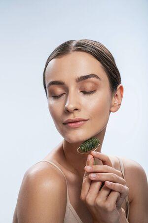 Charming woman using jade roller. Beauty procedures concept