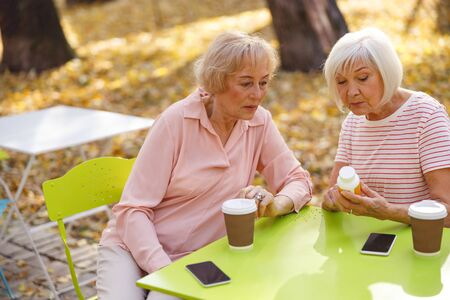 Two aged women sitting at the street cafe table and looking at the small bottle of pills