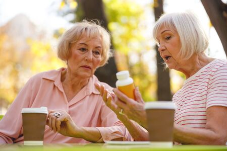 Two old ladies sitting in the park and speaking about the meds one of them holding