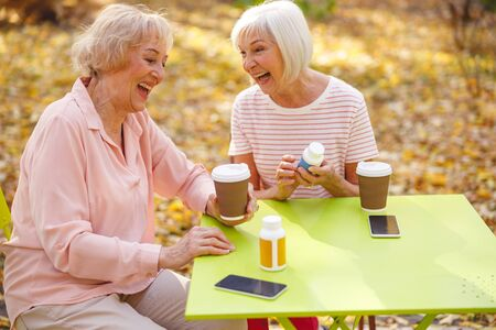 Two jolly aged women sitting at the table outside and laughing