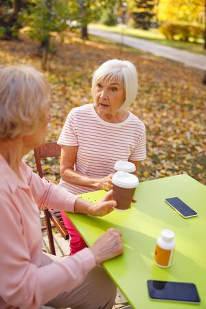 Grey-haired lady being astonished talkink to her friend in the park