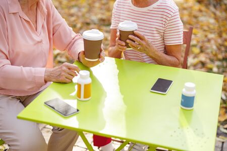 Closee up picture of coffee cups in hands of women sitting at the table in the park