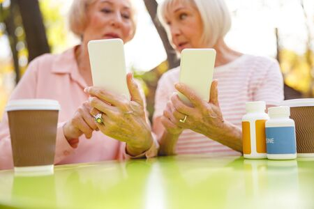 Two old women sitting in the park showing each other their smartphones Zdjęcie Seryjne
