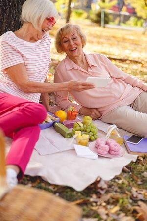 Two cheerful women laughing sitting on the ground and looking at the smartphone