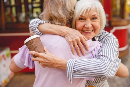 Two happy aged women hugging standing in front of the street cafe Banco de Imagens