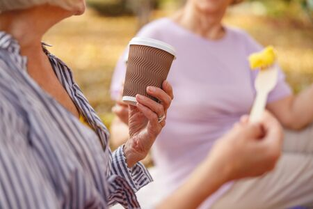 Close up picture of a coffee cup and a piece of fruit in hands of a female