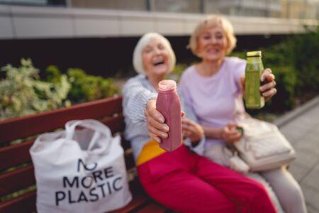 Schöne alte Frauen, die Smoothies beim Sitzen auf einer Bank trinken