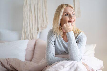 Femme souriante calme regardant pensivement loin avec sa main touchant son menton