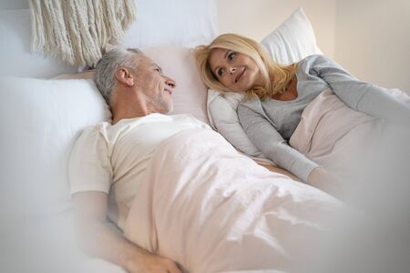 Calm woman and man lying in bed and smiling while talking Stock Photo