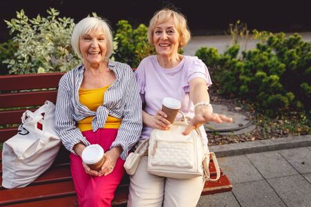 Happy aged ladies laughing and having coffee sitting on a bench