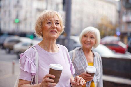 Zwei glückliche Damen, die spazieren gehen und Kaffee trinken