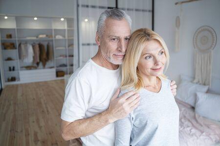 Schönes erwachsenes Paar, das zu Hause in seinem Zimmer steht und lächelt