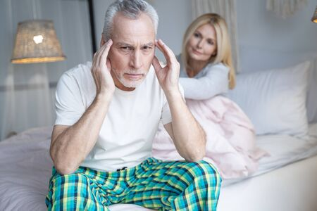 Adult man in pajamas sitting on the bed near his wife and touching his temples