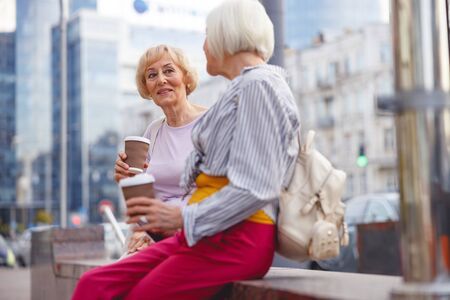 Two beautiful old ladies sitting and drinking coffee in the city centre