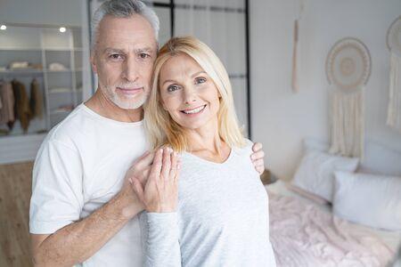 Fröhliche Frau, die mit dem Rücken zu einem Mann im Schlafzimmer steht und lächelt
