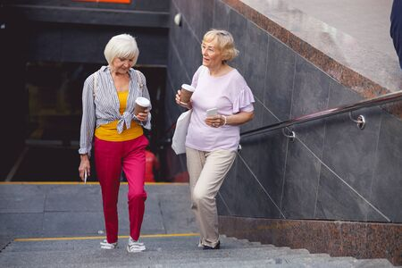 Two aged ladies going out the underpass and drinking coffee