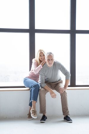 Happy woman and man on the window seat posing for family photo