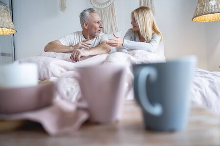 Expressive man and woman sitting in bed and gesturing while talking
