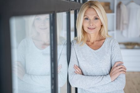 Cheerful lady standing with crossed arms near the window Standard-Bild