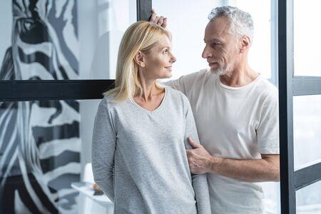 Schönes erwachsenes Paar an der Glastür, das sich ansieht