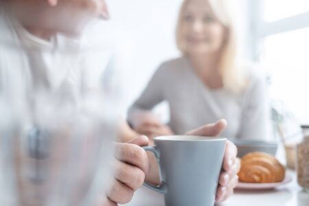 Close up of a man holding a cup. Woman on the background