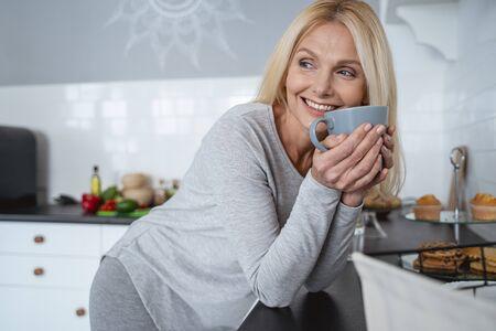 Glückliche Frau in der Küche, die eine Tasse hält und lacht Standard-Bild