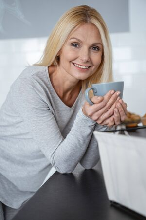Gladsome woman holding a mug while standing in the kitchen and smiling