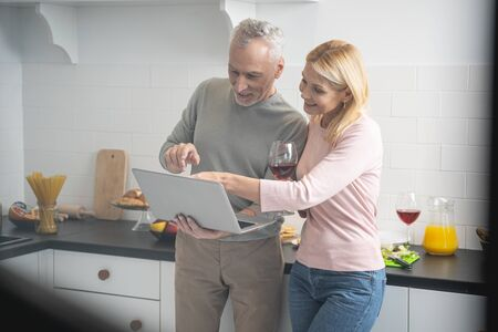 Cheerful man and woman with glasses of wine pointing to the laptop screen and smiling
