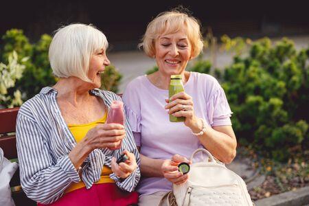 Twee lachende oude vrouwen die op een bankje zitten en smoothies drinken