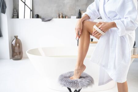 Cropped photo of a woman standing with one foot on a stool