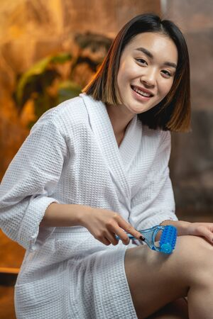Amazing calm Asian woman takes care of her legs. Massage concept
