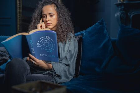 Serious good-looking girl reading attentively an astrology book
